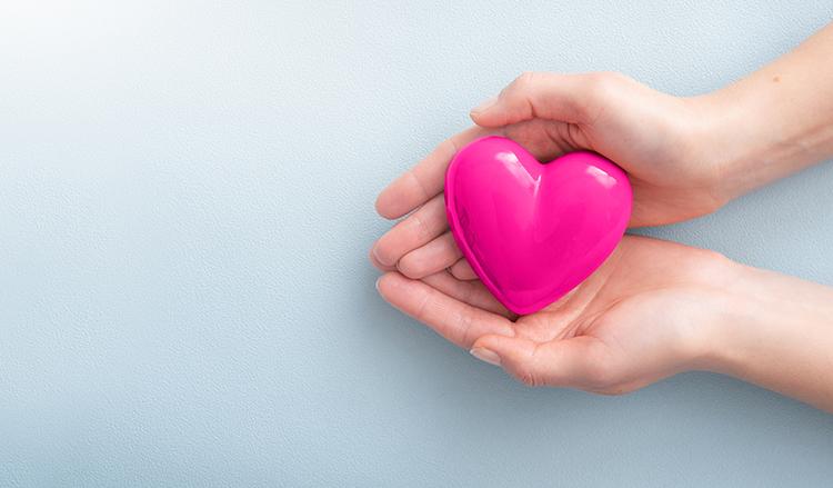 Frau hält ein pinkes Herz in den Händen, es ist nur ein Teil der Unterarme sichtbar.
