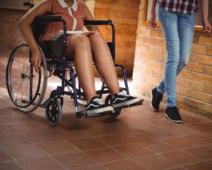 Zwei Frauen gehen bzw. fahren nebeneinander her, eine davon sitzt im Rollstuhl.