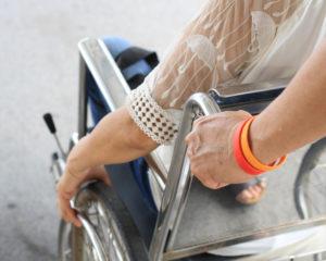 Assistentin schiebt den Rollstuhl einer Assistenznehmerin, es ist ein Teil des Rollstuhls zu sehen und die Arme der Beiden.