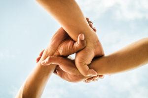 Drei Hände greifen ineinander