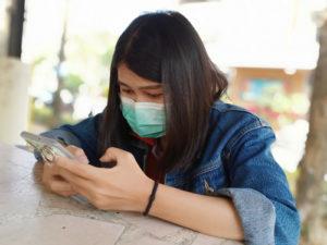 Frau mit Gesichtsmaske schaut auf ihr Handy