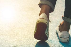 Es sind Schuhe und ein Teil der Beine zu sehen, von einer Person die läuft.