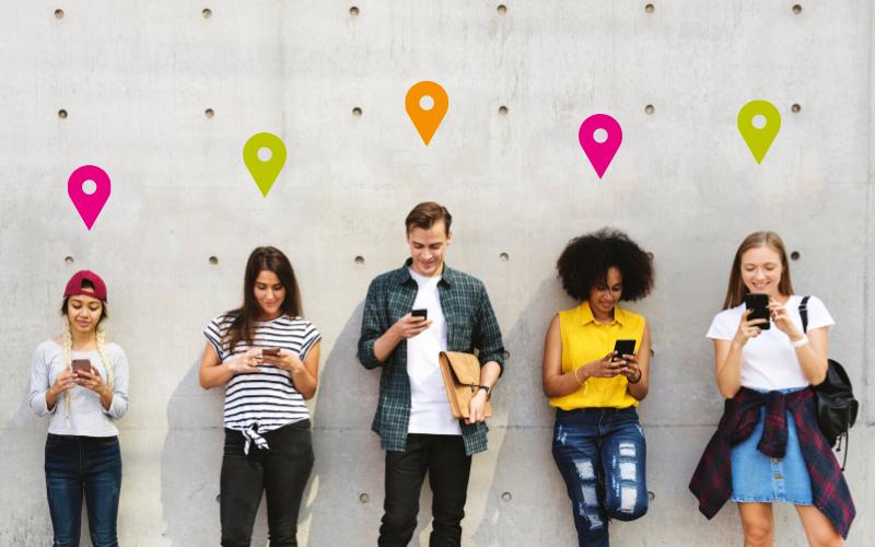 Fünf junge Menschen stehen nebeneinander und bllicken auf ihr Smartphone