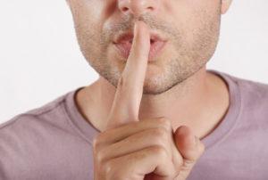 Mann hält sich einen Finger vor den Mund und gestikuliert leise sein
