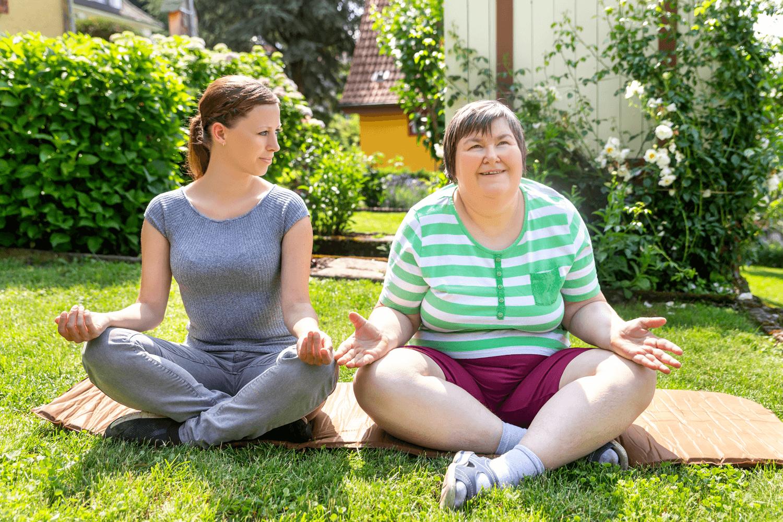 Zwei Frauen machen im Garten Yoga, Beispiel Freizeitassistenz - ava