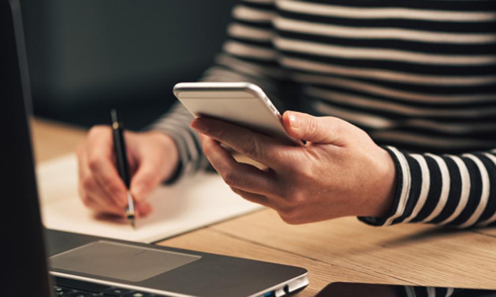 Frau schreibt eine Liste von ihrem Smartphone ab