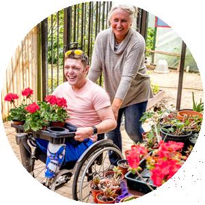 Frau mit Mann im Rollstuhl in Gärtnerei