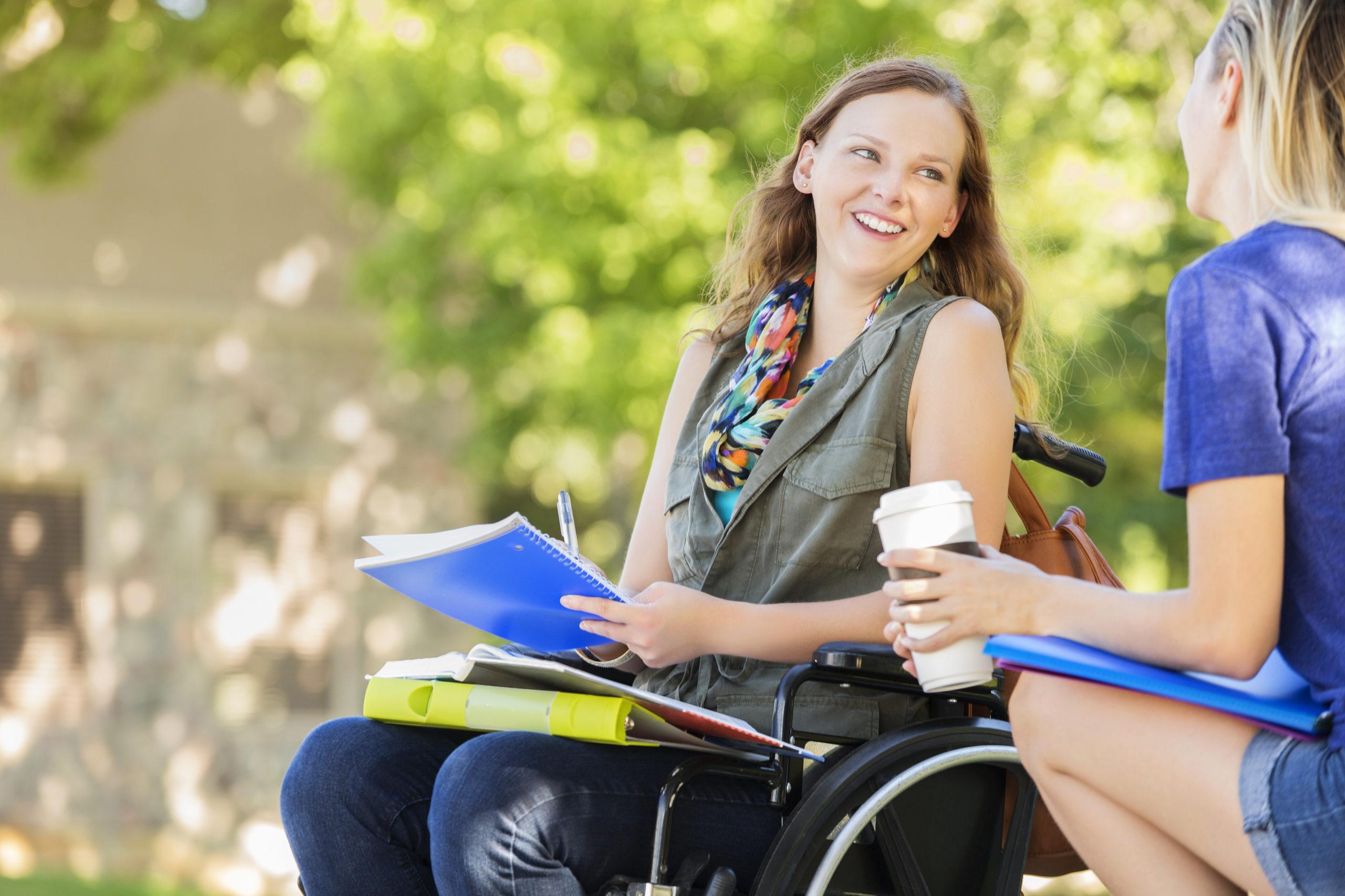 Junge Frau im Rollstuhl spricht mit einer Freundin vor der Unterrichtsstunde. Sie hält einen Laptop und ihre Freundin einen Coffee-to-go Becher.