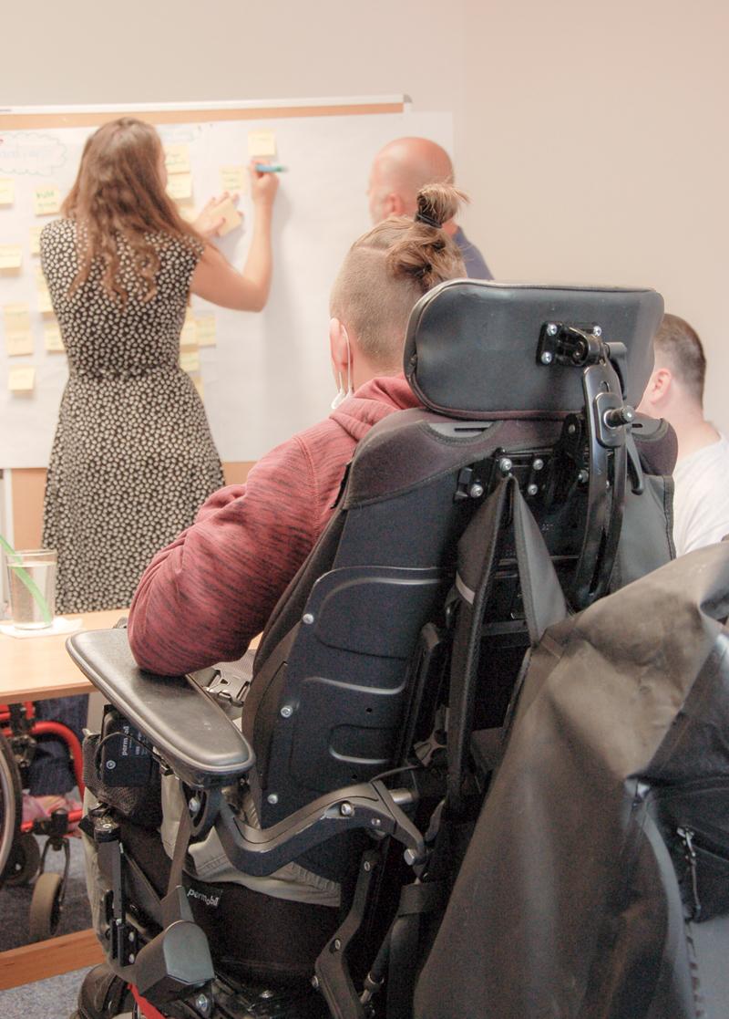 Zwei Menschen stehen vor einer Tafel, ein Mann im Rollstuhl sieht den beiden zu